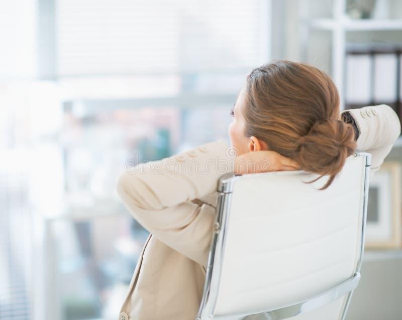 Расслабленная бизнес-леди сидя в офисе стоковое изображение