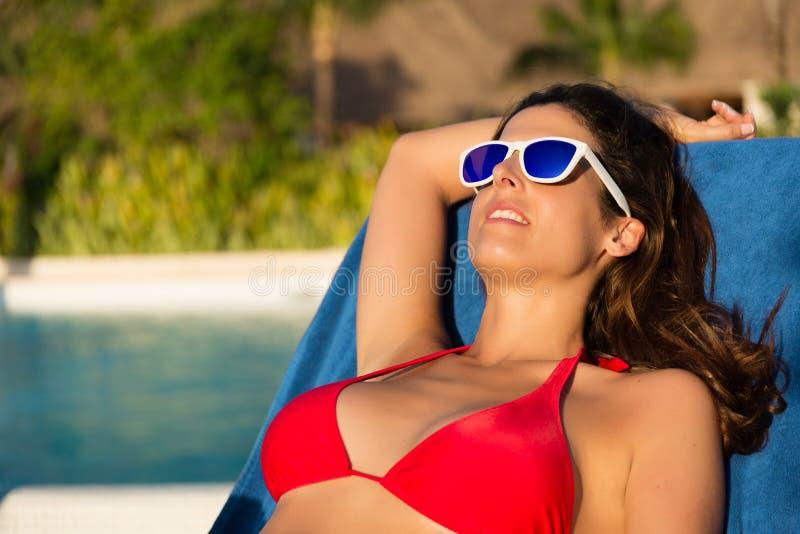 Расслабленная женщина загорая на poolside на летних каникулах стоковое фото rf