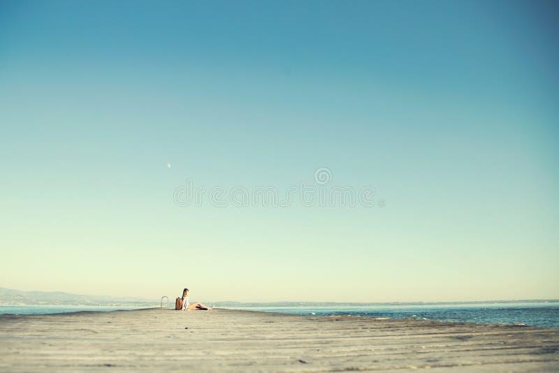 Расслабленная женщина отдыхая после длинного путешествия с ее большим чемоданом стоковое изображение