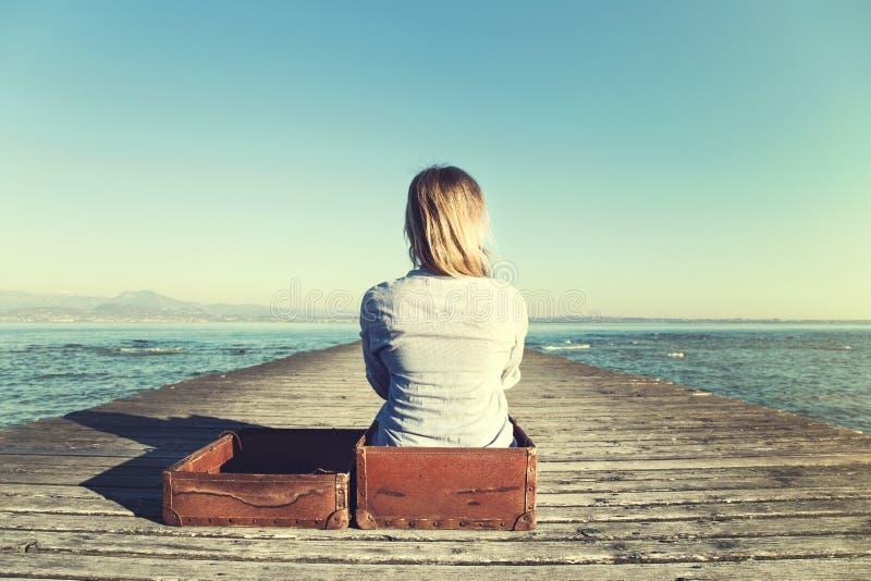 Расслабленная женщина сидя в ее большом чемодане после длинного путешествия стоковое изображение rf