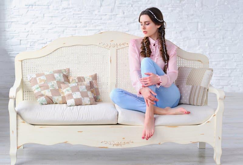 Расслабленная женщина сидя на винтажной софе стоковое фото rf