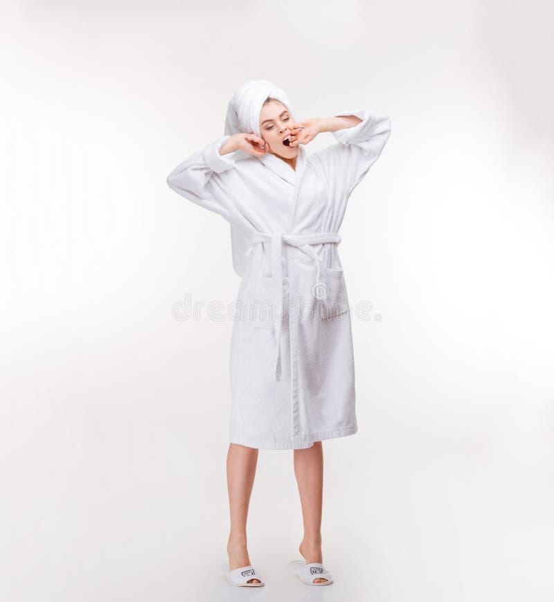 Расслабленная женщина с полотенцем на ее голове протягивая и зевая стоковые фотографии rf