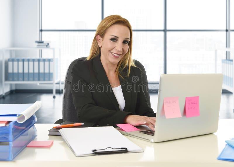 Расслабленная женщина 40s с усаживанием светлых волос усмехаясь уверенно на стуле офиса работая на портативном компьютере стоковое изображение