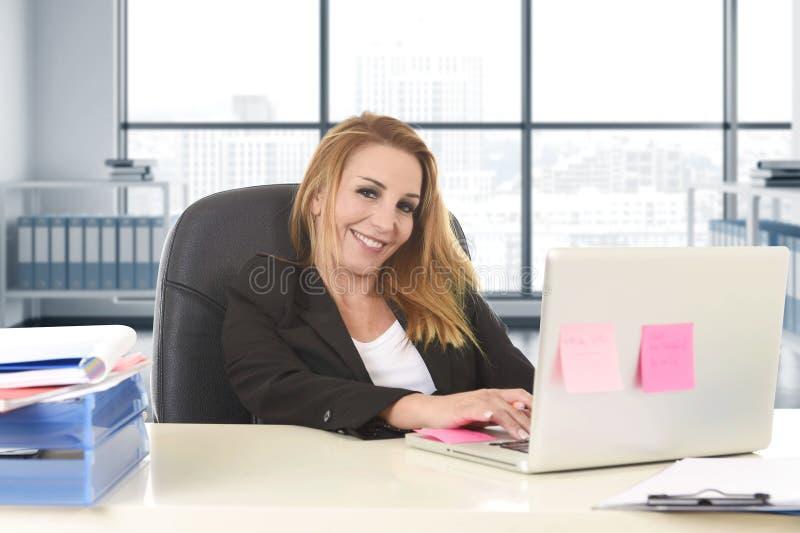 Расслабленная женщина 40s с усаживанием светлых волос усмехаясь уверенно на стуле офиса работая на портативном компьютере стоковые изображения