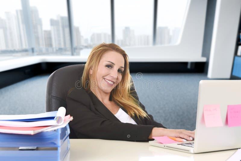 Расслабленная женщина 40s с усаживанием светлых волос усмехаясь уверенно на стуле офиса работая на портативном компьютере стоковые фото
