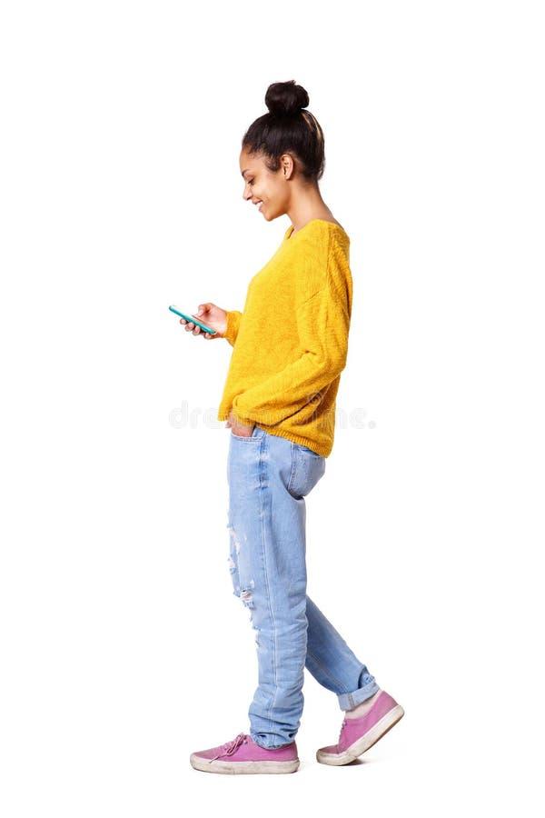 Расслабленная молодая африканская женщина используя мобильный телефон стоковая фотография