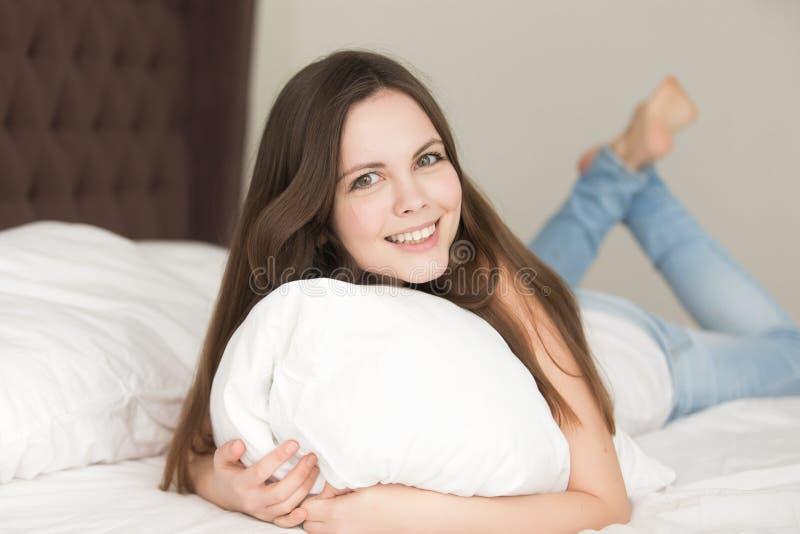 Расслабленная молодая женщина лежа в кровати на животе стоковая фотография rf