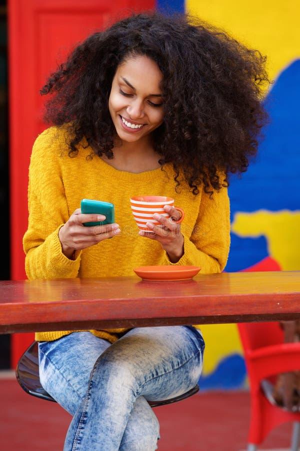 Расслабленная молодая женщина используя мобильный телефон на кофейне стоковое изображение