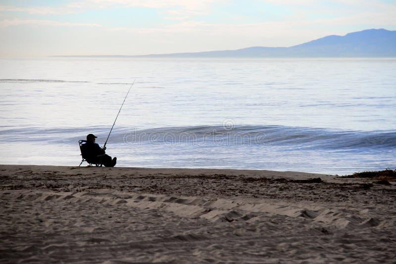 Расслабленная рыбная ловля рыболова на пляже стоковая фотография rf
