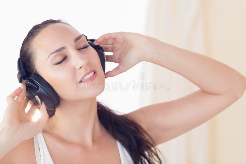 Расслабленное брюнет сидя на кровати слушая к музыке стоковое изображение