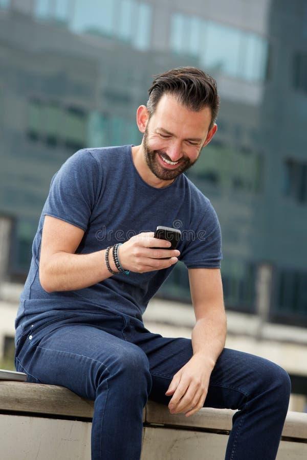 Расслабленное зрелое текстовое сообщение чтения человека на мобильном телефоне стоковые изображения