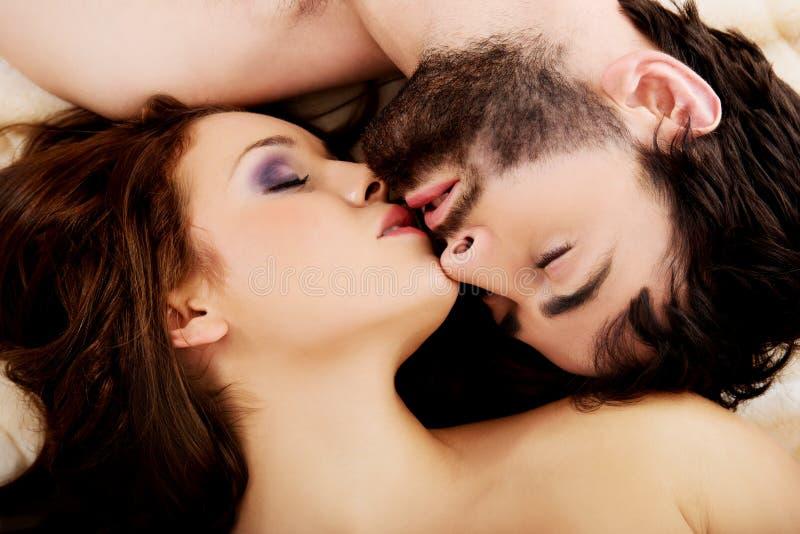Расслабленные молодые пары целуя в кровати стоковое фото