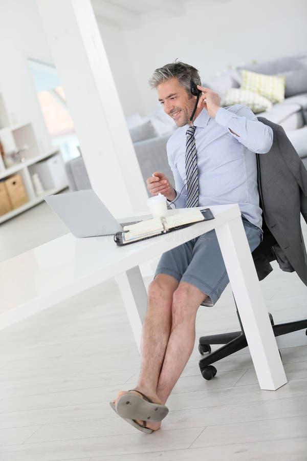 Расслабленный бизнесмен звоня видео- дома стоковая фотография