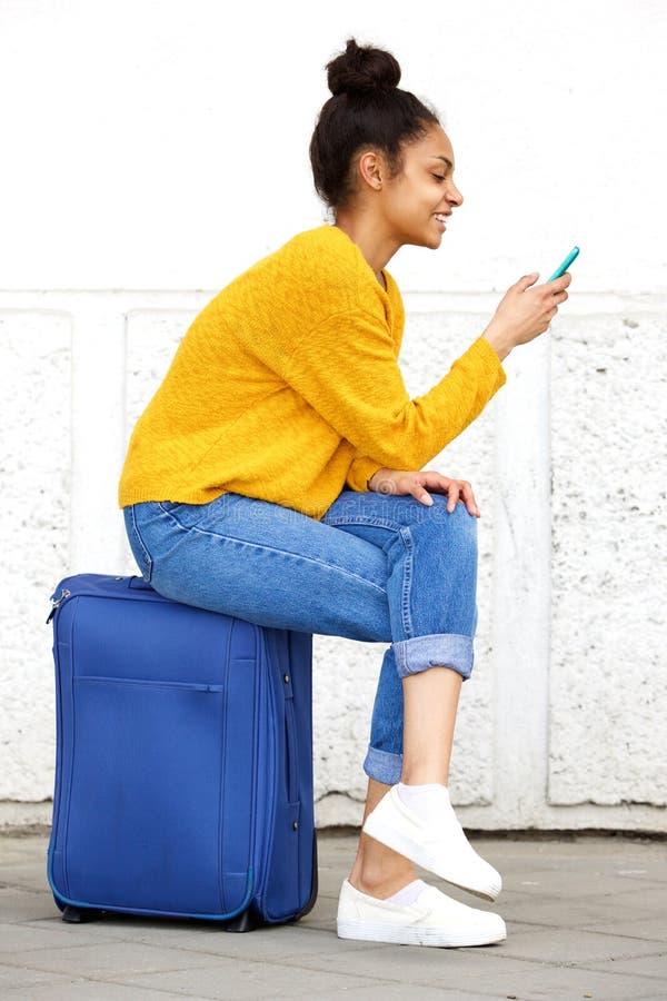 Расслабленный женский путешественник сидя на чемодане и используя мобильный телефон стоковые изображения