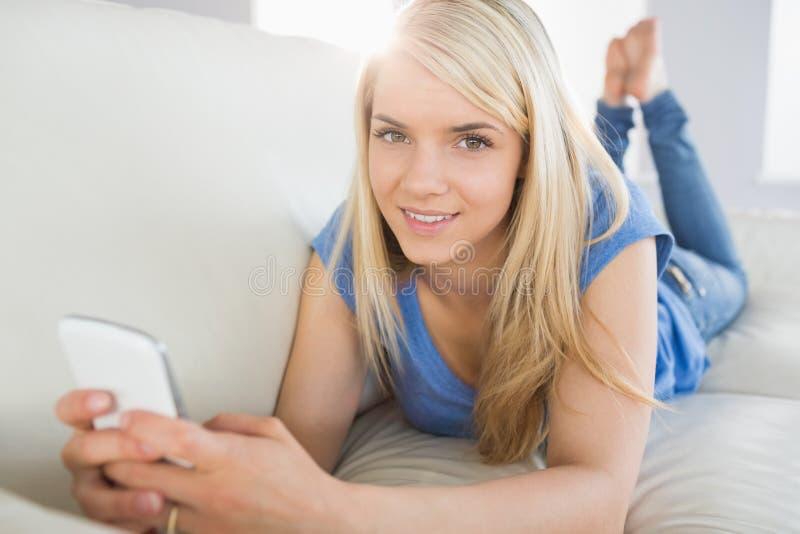 Расслабленный красивый обмен текстовыми сообщениями женщины в живущей комнате стоковая фотография