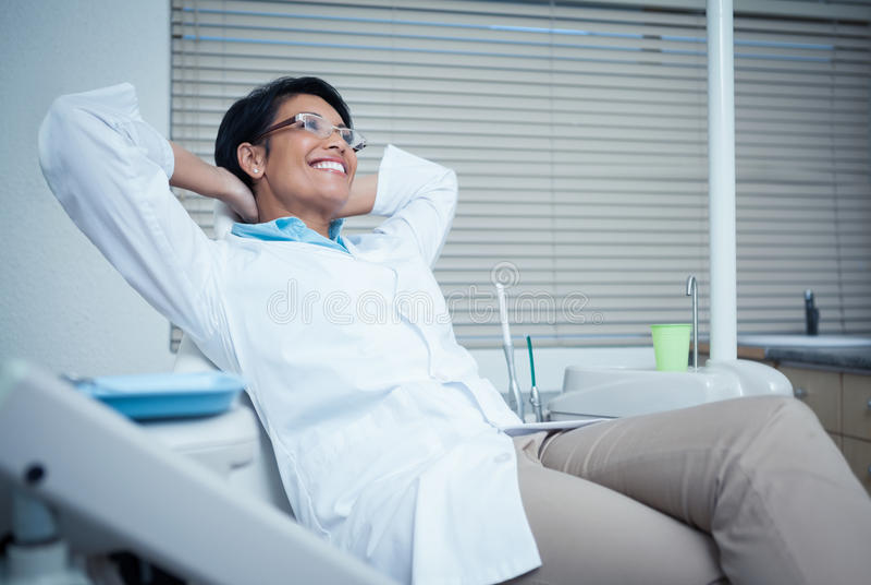 Расслабленный усмехаясь женский дантист сидя на стуле стоковые фотографии rf