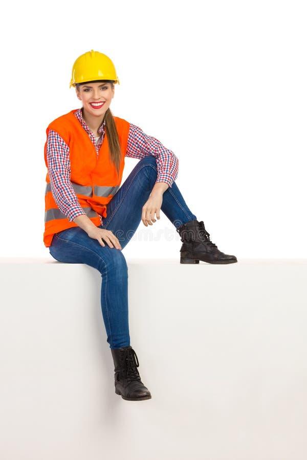 Расслабленный усмехаясь женский рабочий-строитель сидя на верхней части стоковое изображение