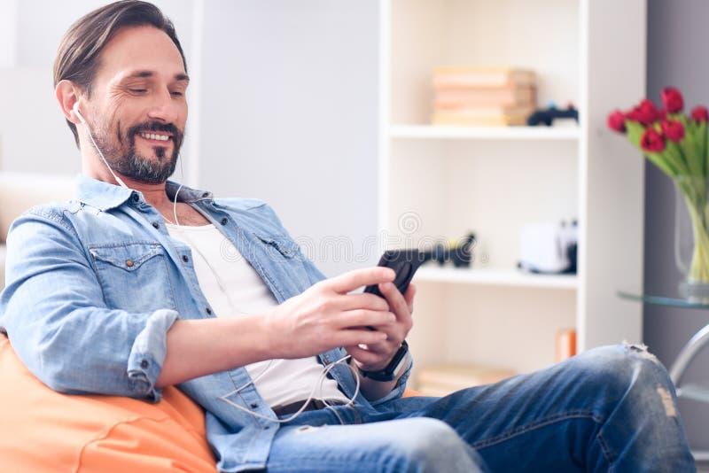 Расслабленный человек используя наушники и умный телефон стоковые изображения
