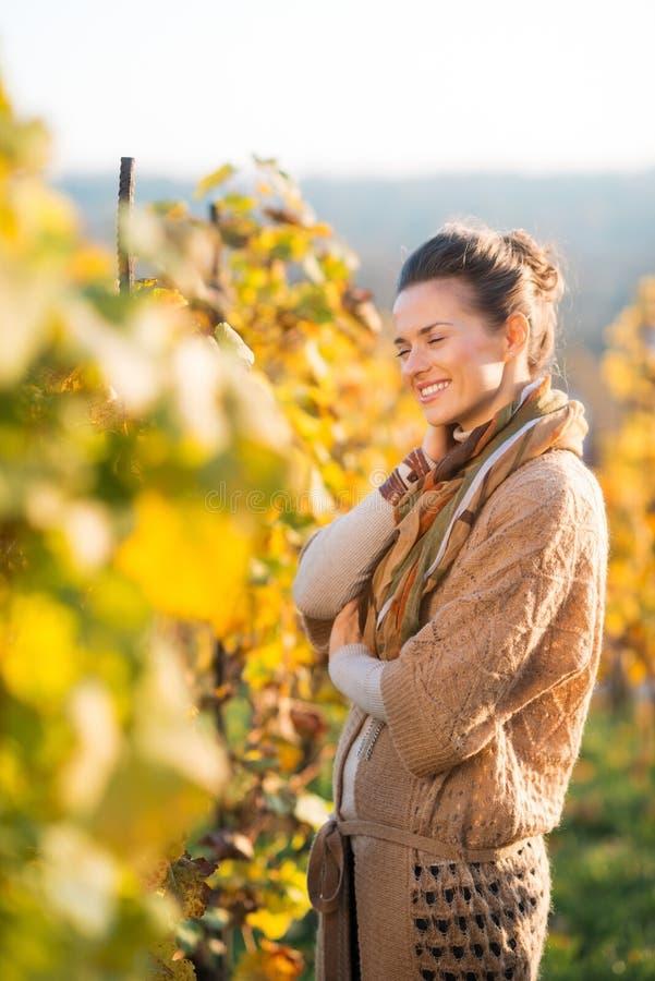Расслабленный winegrower женщины стоя в винограднике outdoors в осени стоковая фотография