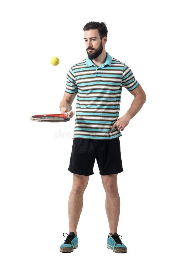 Расслабляющий теннисист в шарике рубашки поло отскакивая с ракеткой стоковое изображение rf
