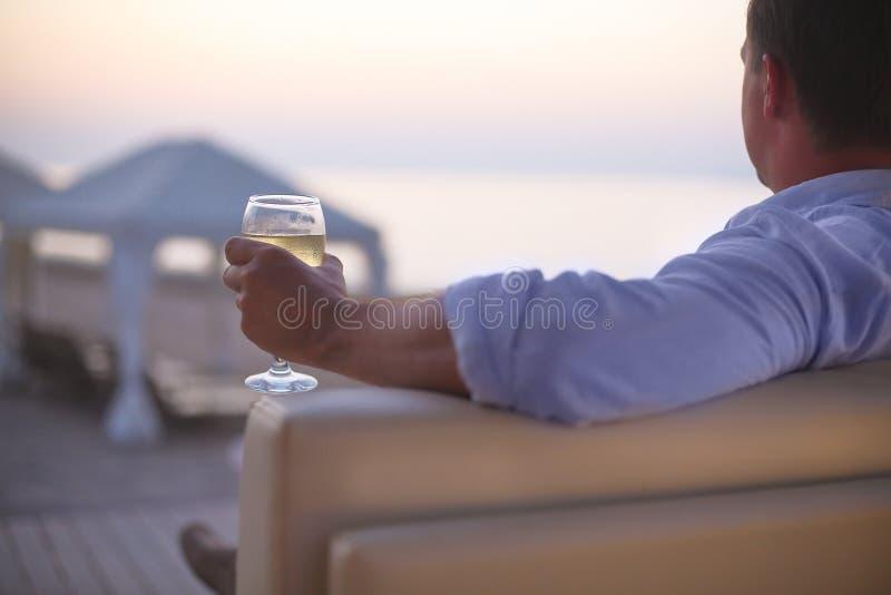 Расслабляющий человек с стеклом белого вина на пляже стоковое изображение rf