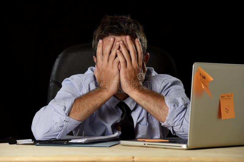 Расточительствованный стресс работы утомленного бизнесмена страдая потревожился занятое в офисе поздно на ноче с портативным комп стоковое изображение