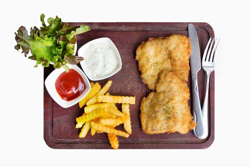 Растрачивать стейк рыб, который служат с французскими фраями на белом b стоковые изображения