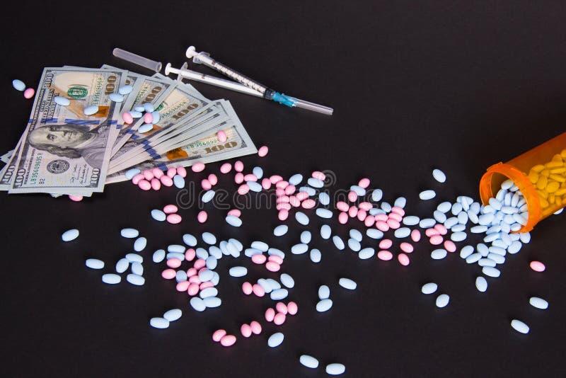 Расходы лекарств Разбросанные пилюльки рядом с шприцем и 100 долларовыми банкнотами стоковое фото rf