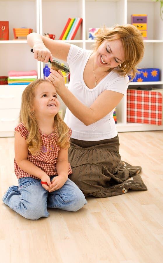 расчесывать женщину волос девушок маленькую стоковое изображение