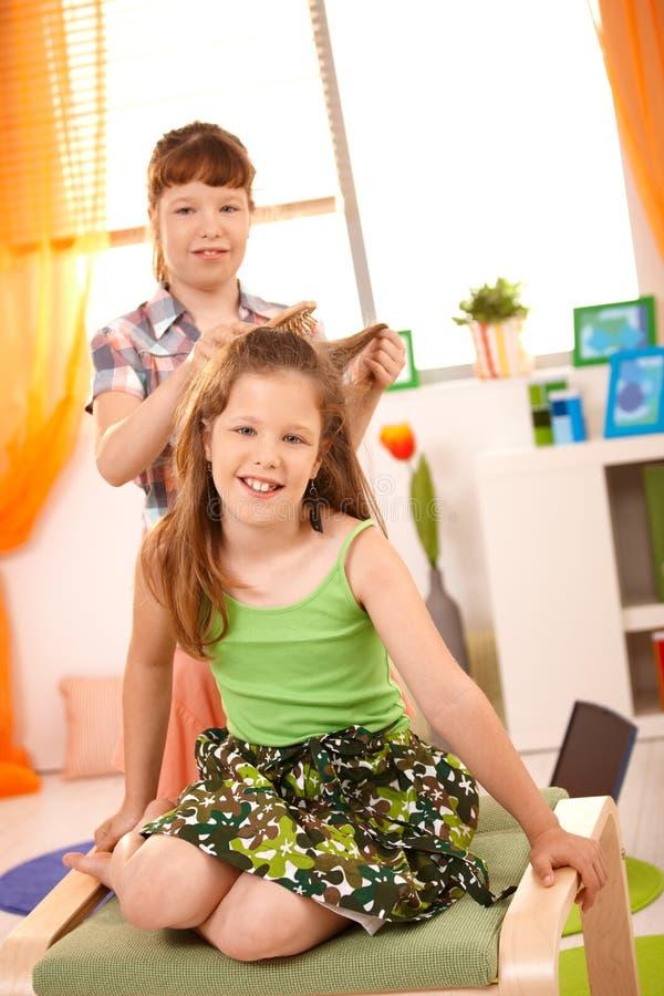 расчесывающ волос девушок потехи имея детенышей стоковые фотографии rf