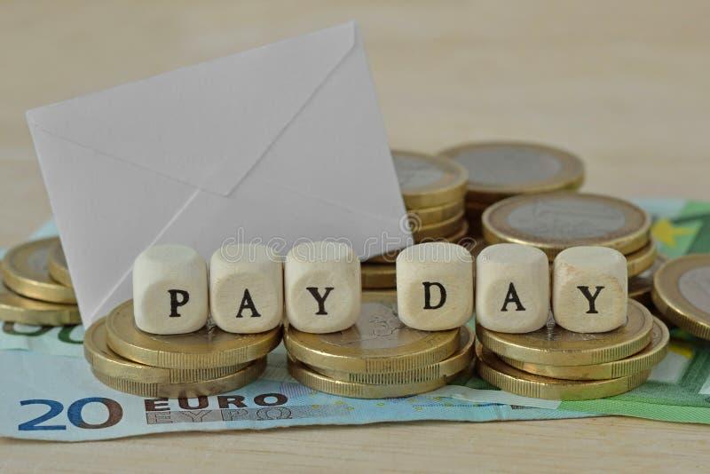 Расчетный день слов написанный с деревянными кубами над монетками и bankno евро стоковая фотография rf