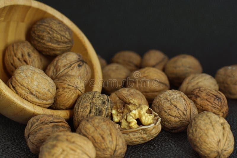 Расчехлены грецкие орехи разбросаны от бамбукового шара на черной предпосылке, одном стоковое изображение rf
