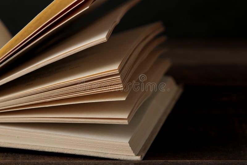 Расширенный конец книги на коричневом деревянном столе и на черной предпосылке записывает старую Образование школа изучение стоковая фотография