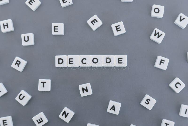 Расшифруйте слово сделанное квадратного слова письма на серой предпосылке стоковые изображения