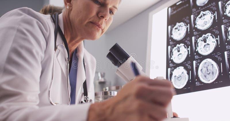 Радиолог постаретый серединой женский смотря через микроскоп стоковое фото rf
