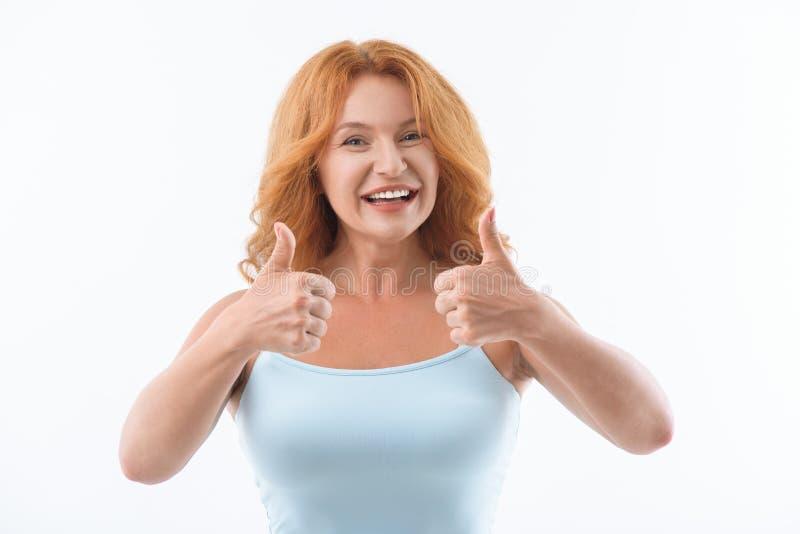 Радостная дама показывая одобренный знак стоковые изображения