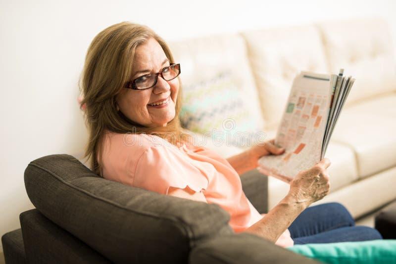 Радостная выбытая старшая женщина держа газету стоковые фото