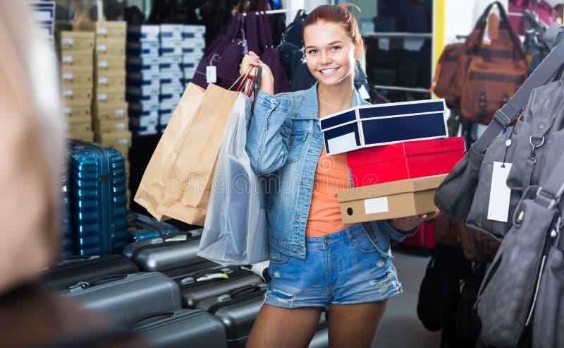 Радостная девушка подростка держа коробки в бутике ботинок стоковые изображения