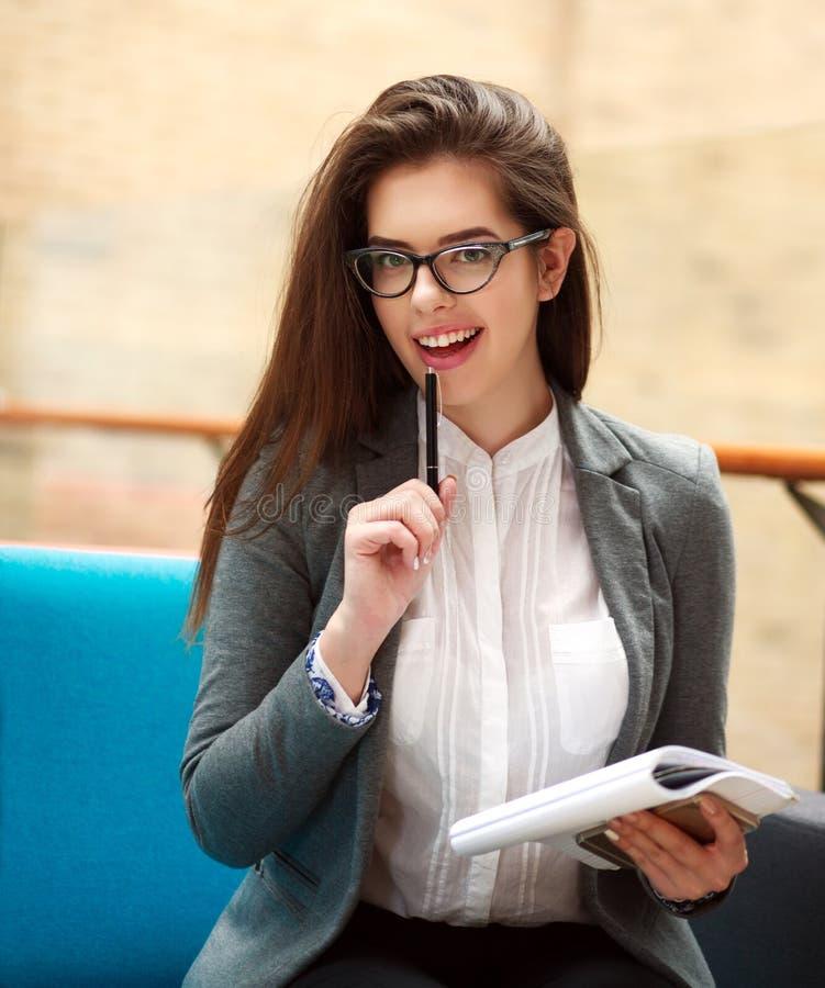 Радостная девушка студента с ручкой и блокнотом имеет идею стоковые фото