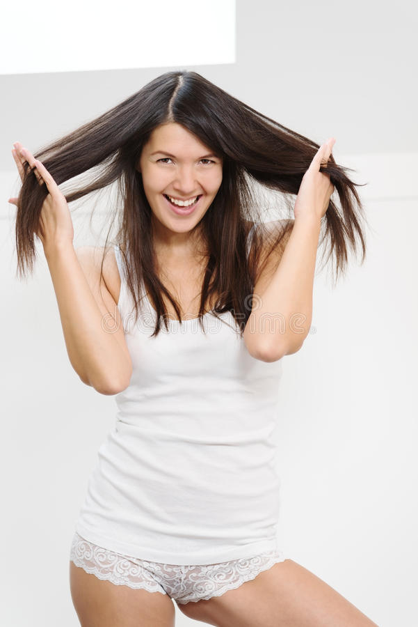 Радостная женщина играя с ее волосами стоковое изображение rf