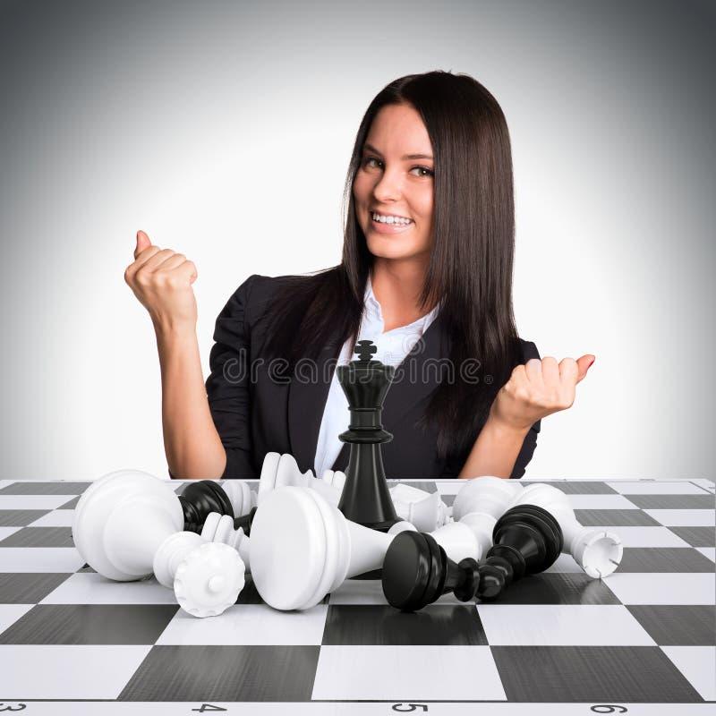 Радостная коммерсантка выигрывает шахмат и подняла его стоковое фото