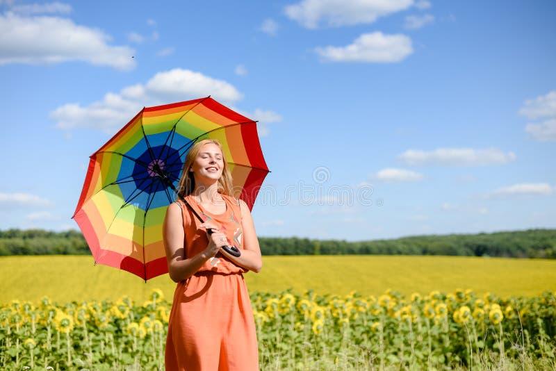 Радостная красивая молодая дама с зонтиком радуги стоковые фотографии rf