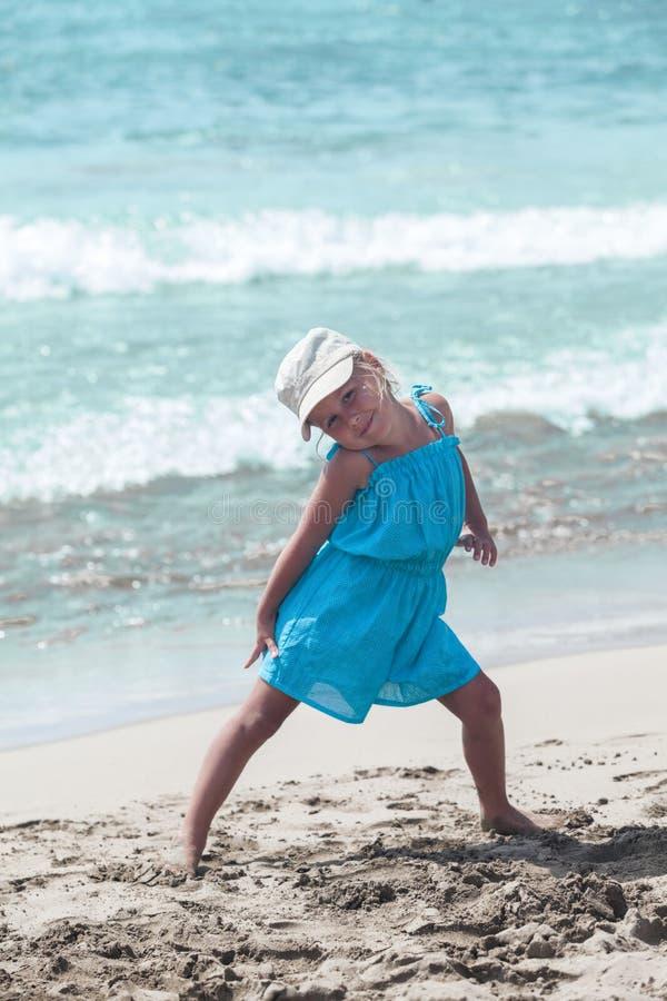 Радостная маленькая девочка представляя на песчаном пляже стоковое фото