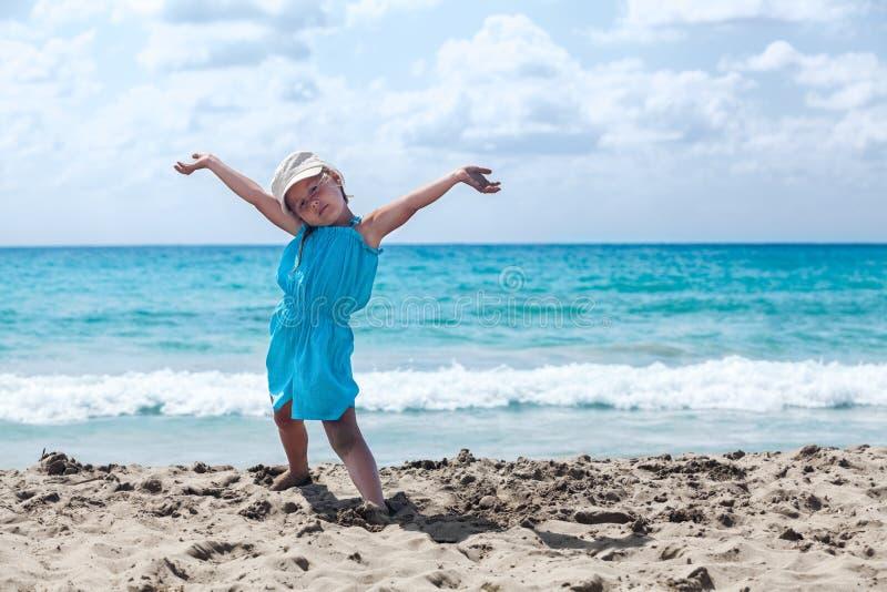 Радостная маленькая девочка с руками поднимает ослаблять на песчаном пляже стоковые изображения