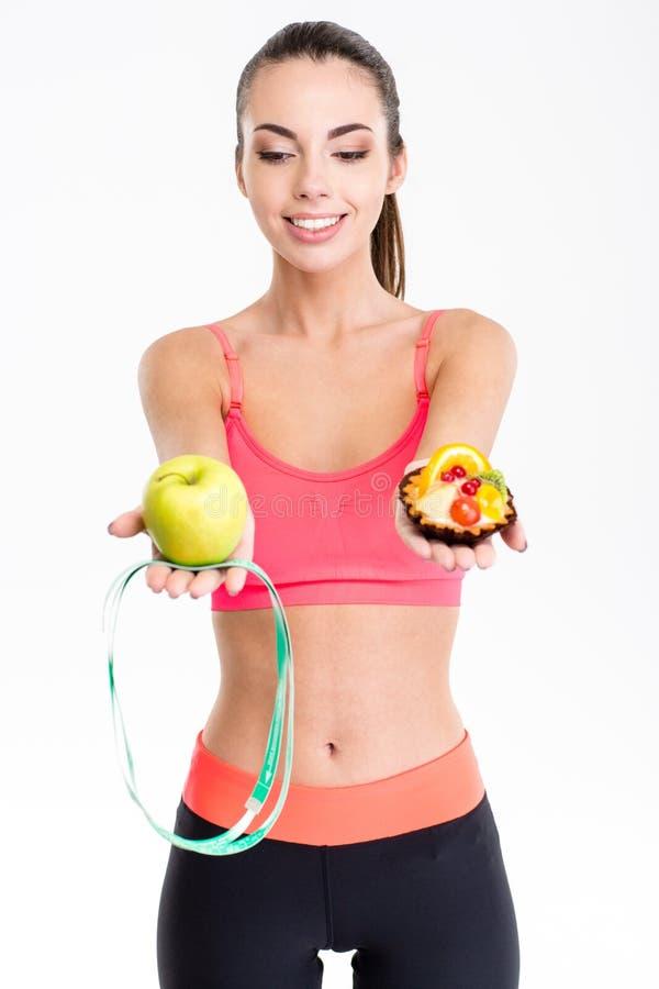 Радостная милая женщина фитнеса принимая решениее между яблоком и тортом стоковая фотография rf