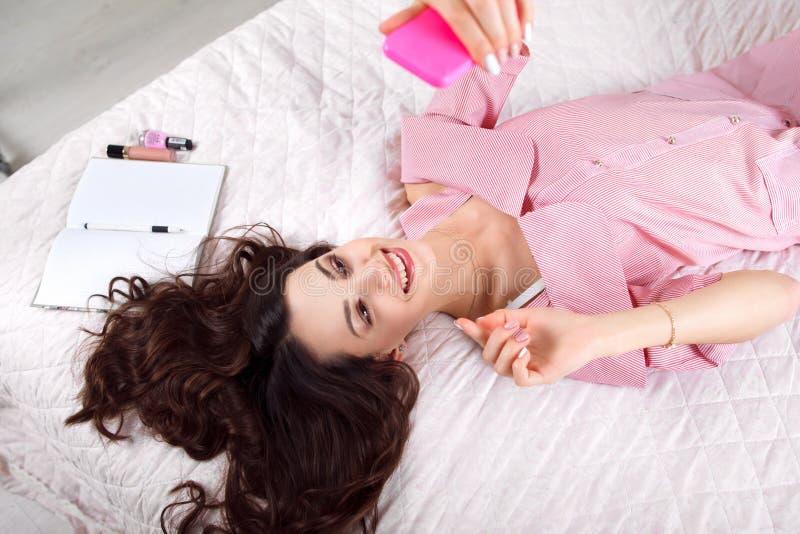 Радостное брюнет делая selfie лежа на кровати стоковое изображение rf