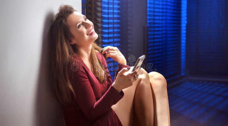 Радостное брюнет отправляя СМС ее парень стоковые изображения