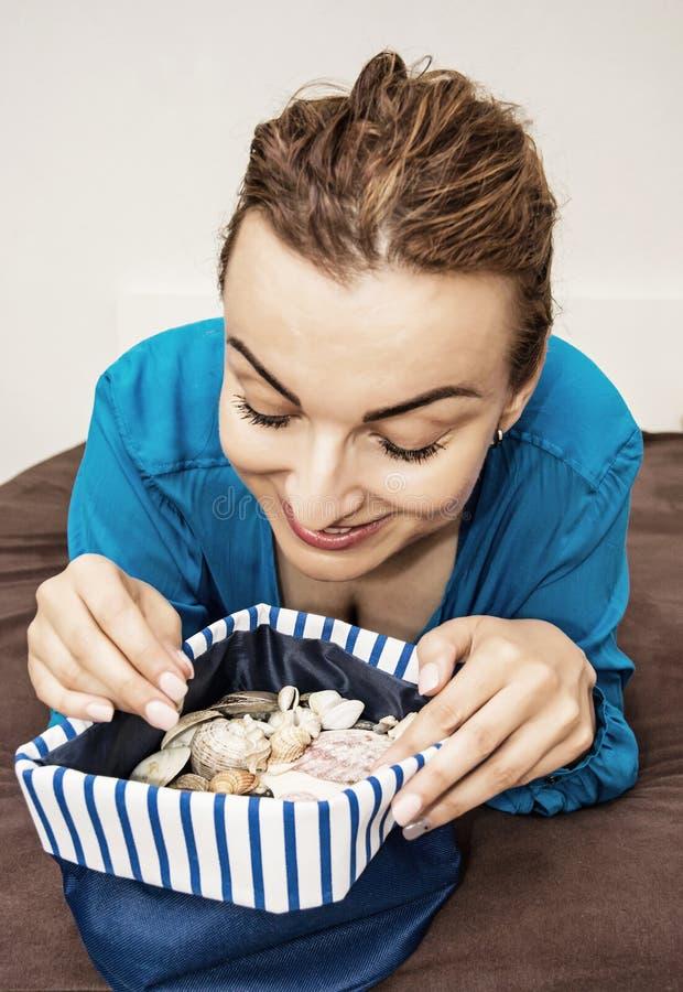 Радостное кавказское брюнет с различными раковинами в сумке матроса, bea стоковая фотография rf