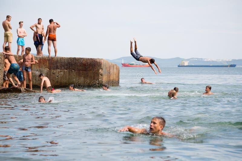 Радостные дети скача и ныряя в море от старого дока стоковая фотография
