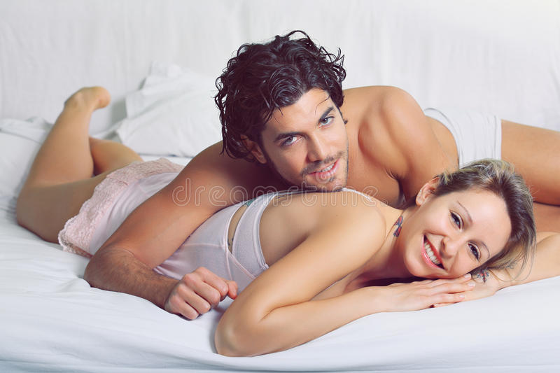 Радостные пары усмехаясь в кровати стоковые изображения
